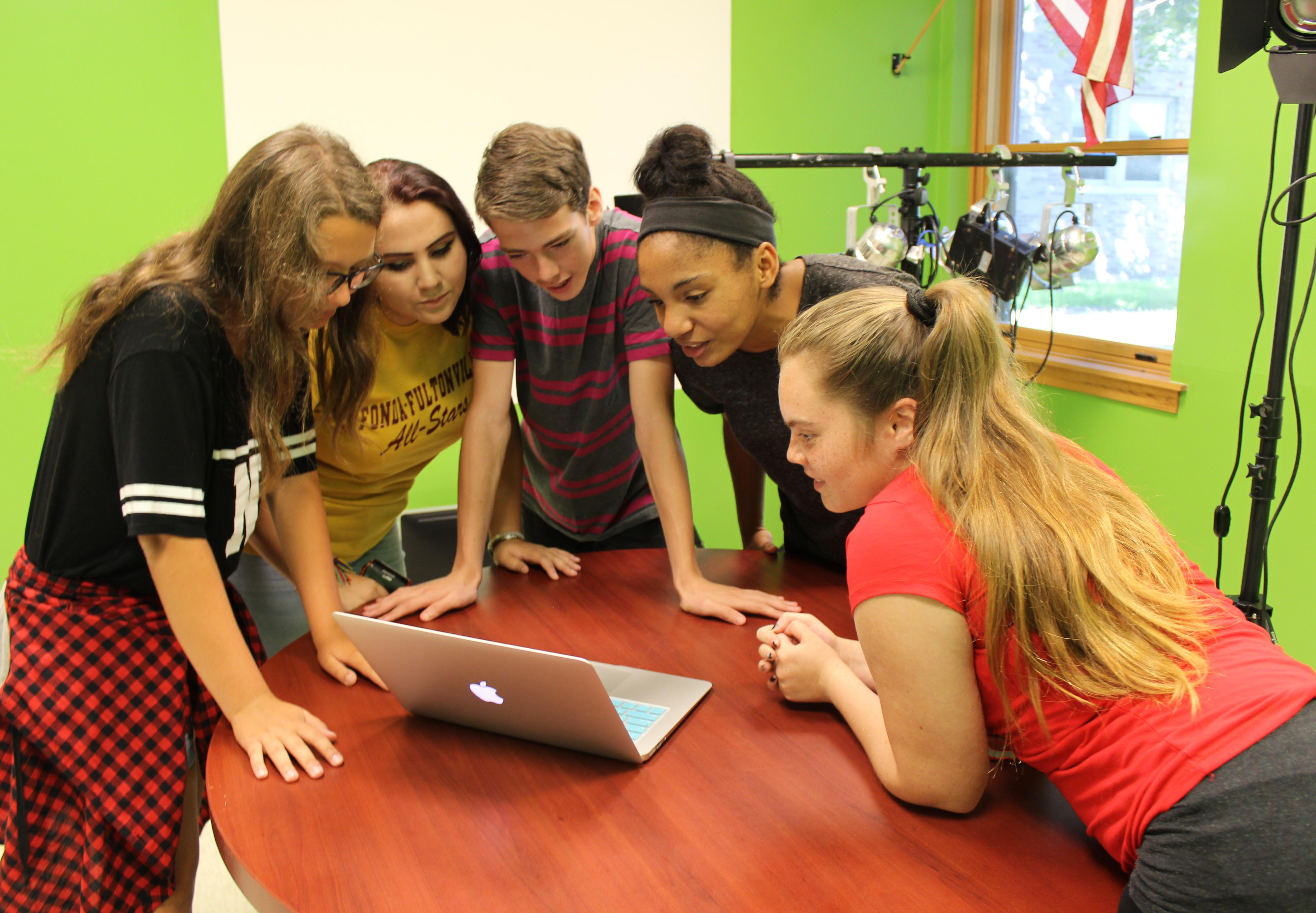 Five students stand around a laptop.