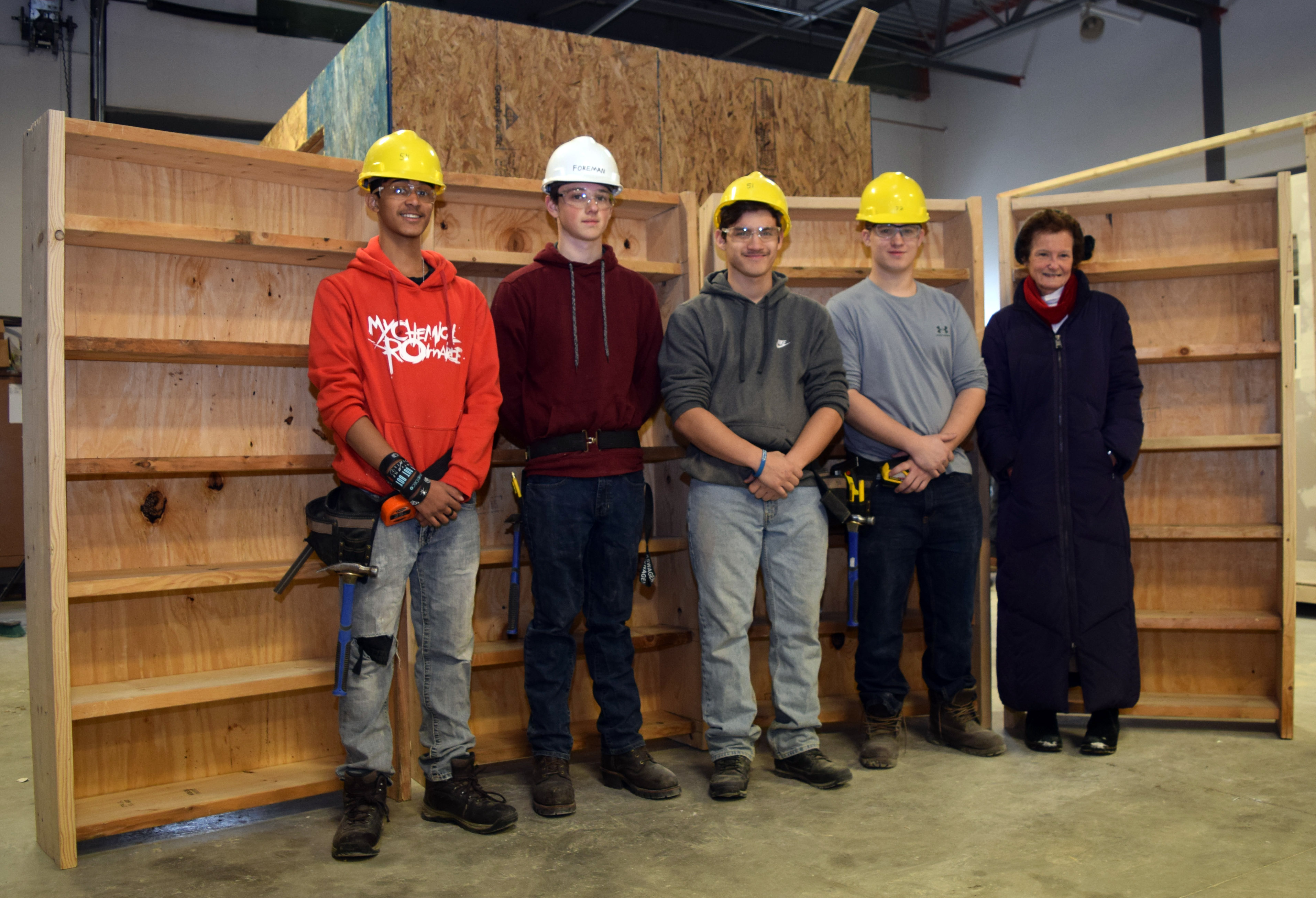 Four students wearing hard hats and an adult stand in front of four six-foot tall bookcases.