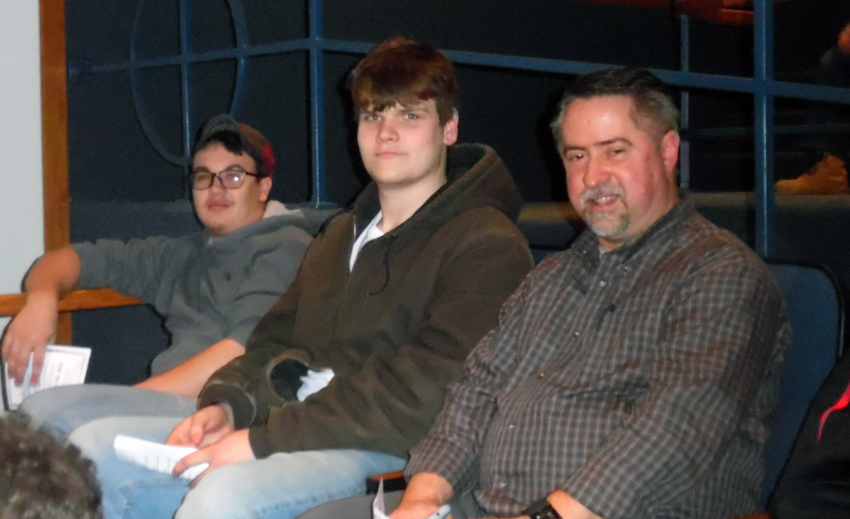 Sawyer, center, sits with two other in auditorium chairs.