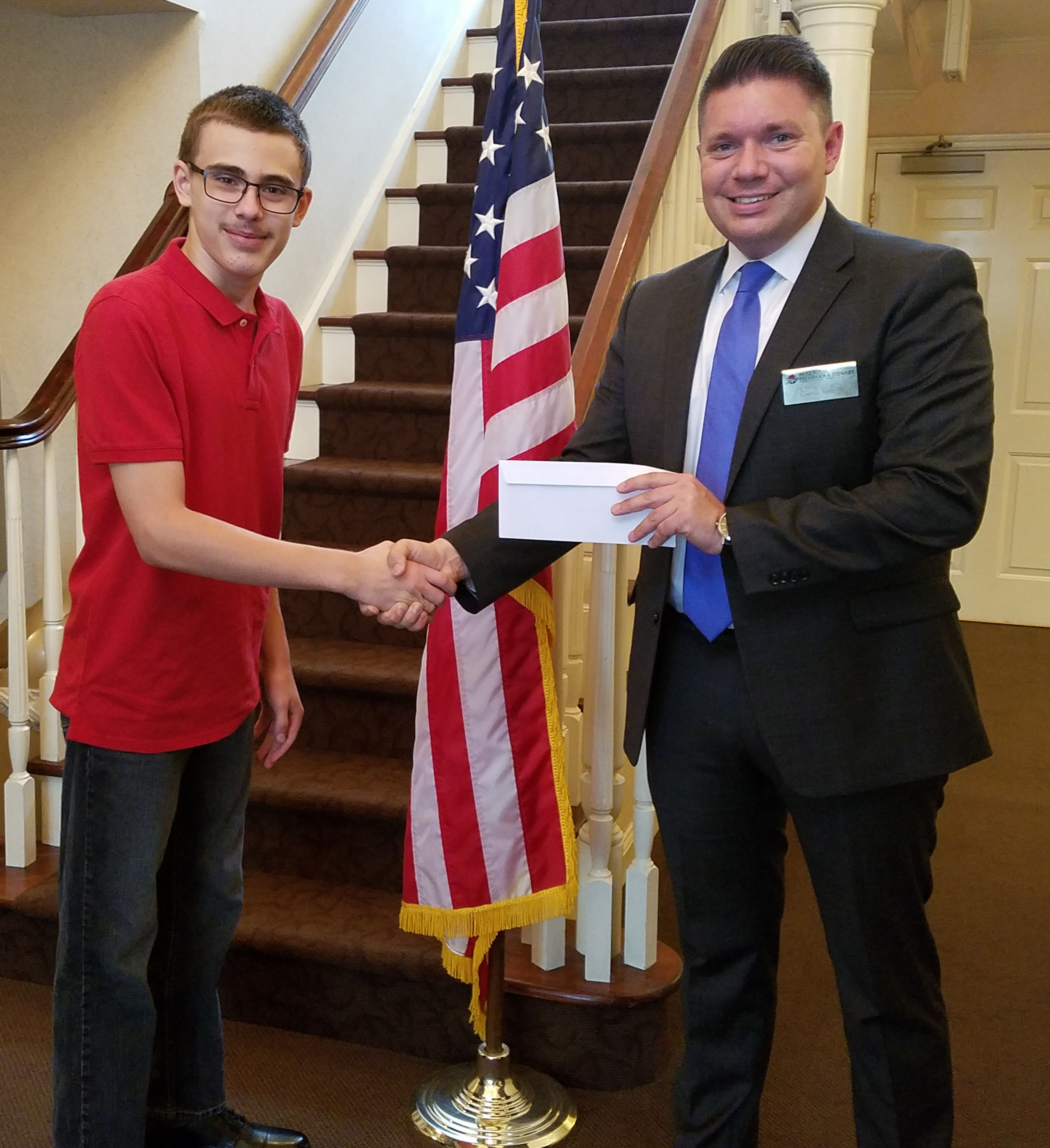 Garrick shakes hands with a funeral home representative who hands him an envelope