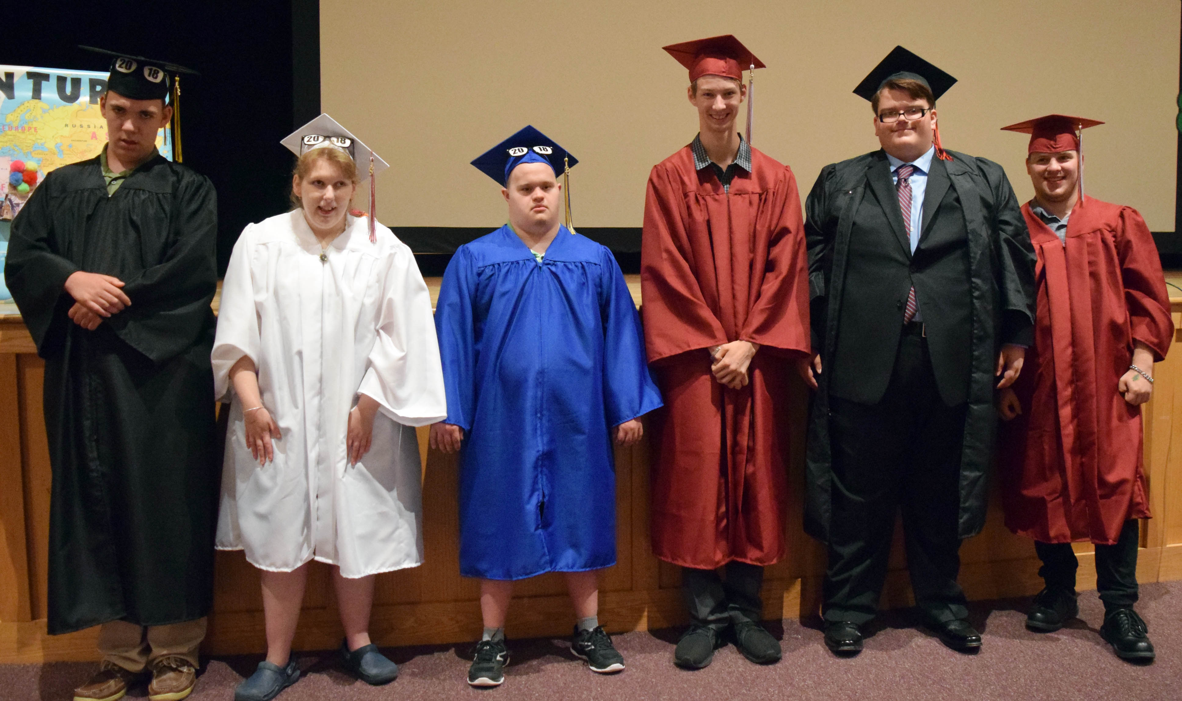 Six graduates stand in a row.