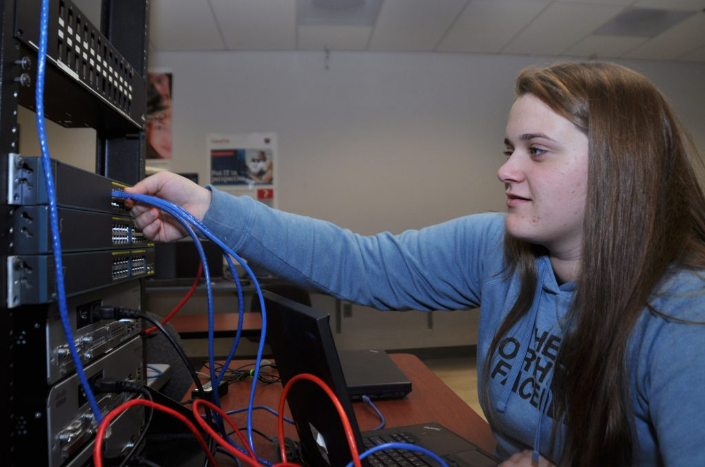 A student connects a cable into a computer tower.