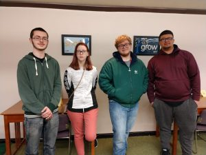 Four of the five students selected for membership into Phi Theta Kappa pose in the library.