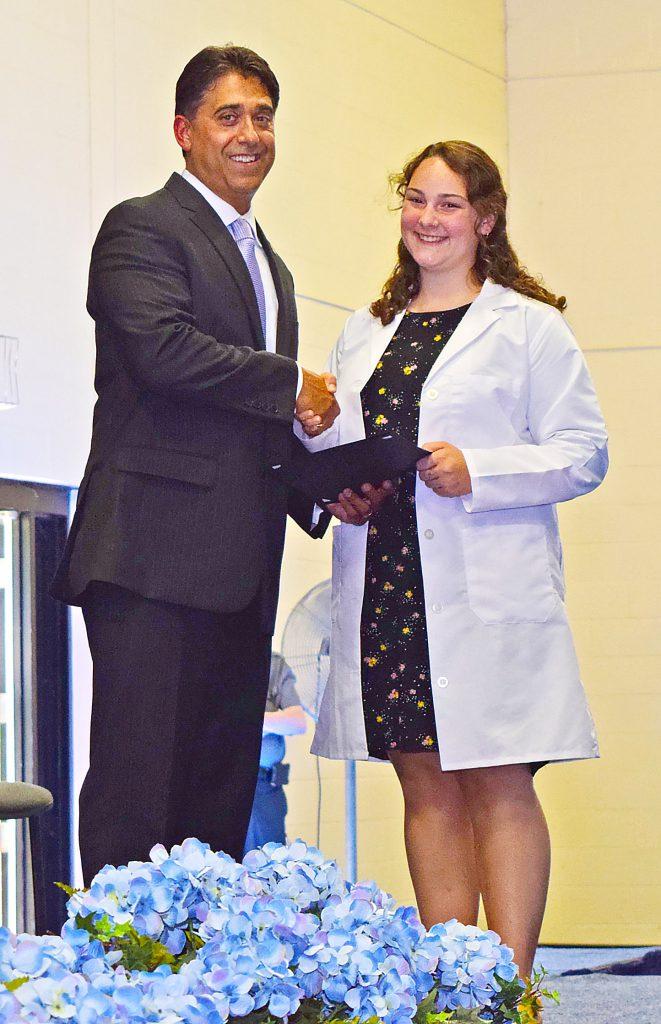 DeTraglia and a student shake hands