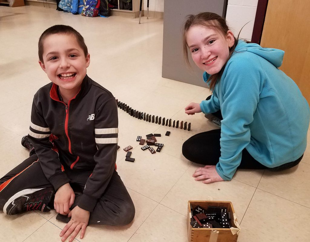 Two students set up Dominoes to knock down.
