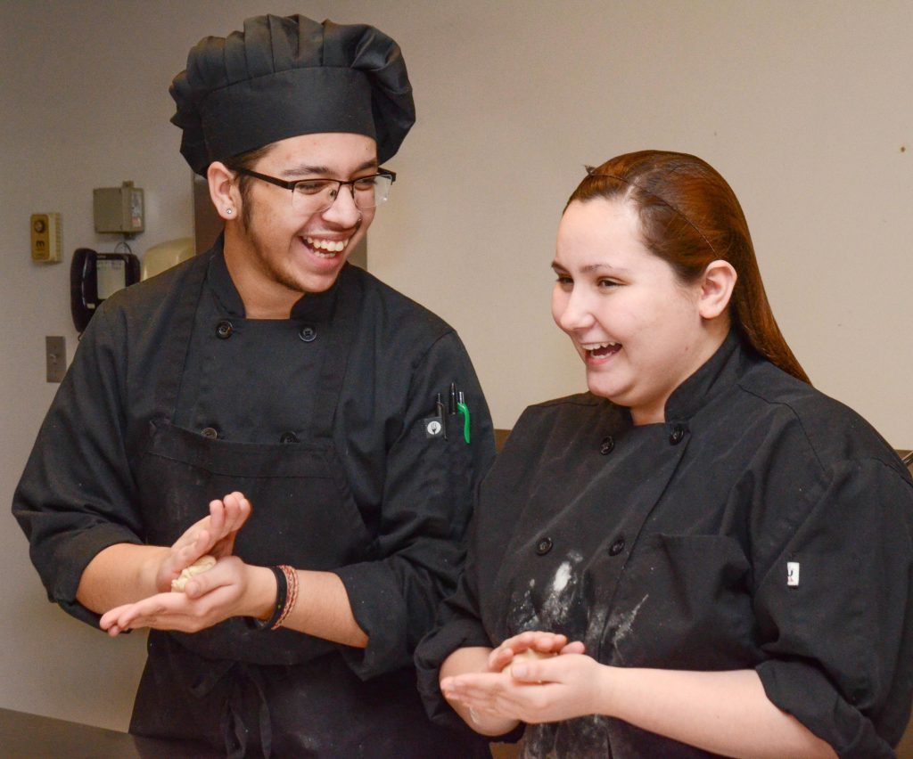 Two students in culinary uniforms roll dough in their hands and laugh together
