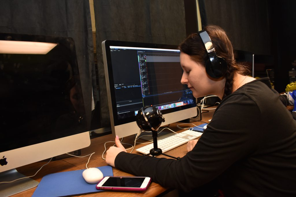 A student wears headphones and speaks into a recording device