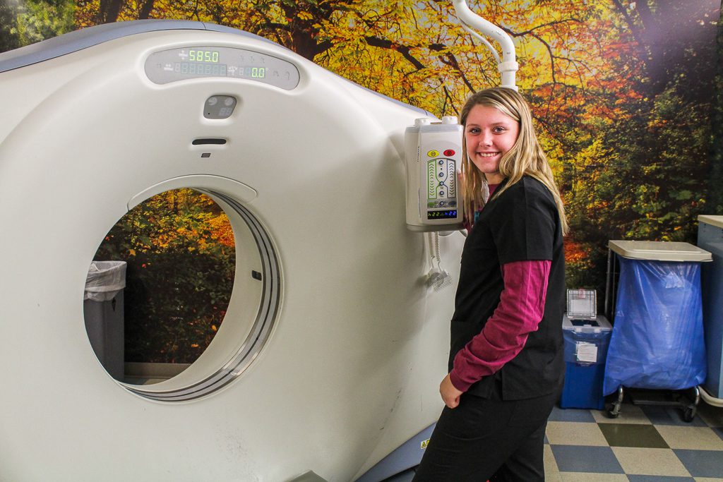 A student poses near an imaging machine
