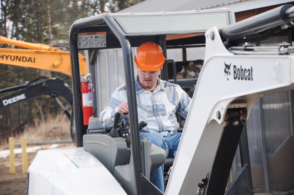 A student operates a loader