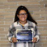 Alanis Roman standing holding her award