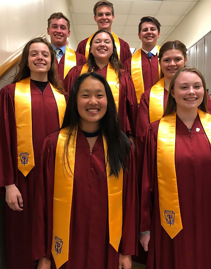 8 high school students pose for a photo wearing gowns and honor society sashes
