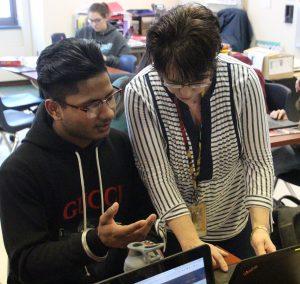 A teacher helps a student at a computer