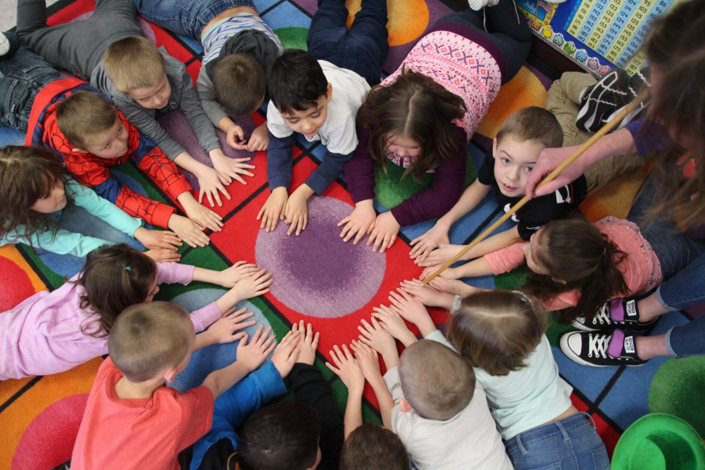 Student lay in a circle putting their hands in the middle