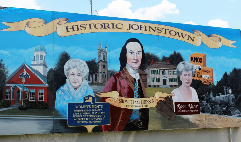 A photo of the Johnstown mural featuring Sir William Johnson, Elizabeth Cady Stanton, Rose Knox, the 1772 courthouse, Johnson Hall, a church Knox Gelatin and a train