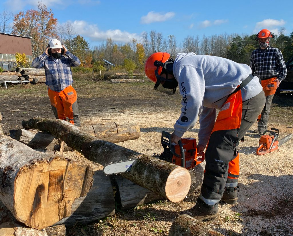 A student cuts a log with a chainsaw as an instructor and another student look on.
