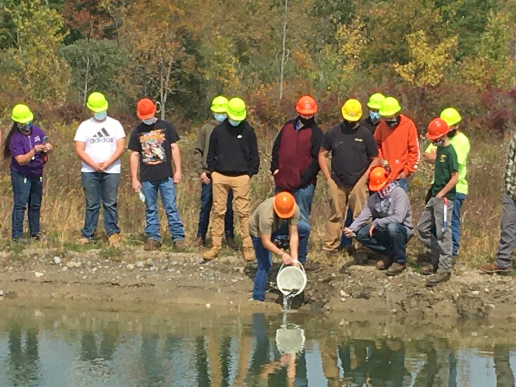 Students stand by a pond as an instructor add fish from a bucket