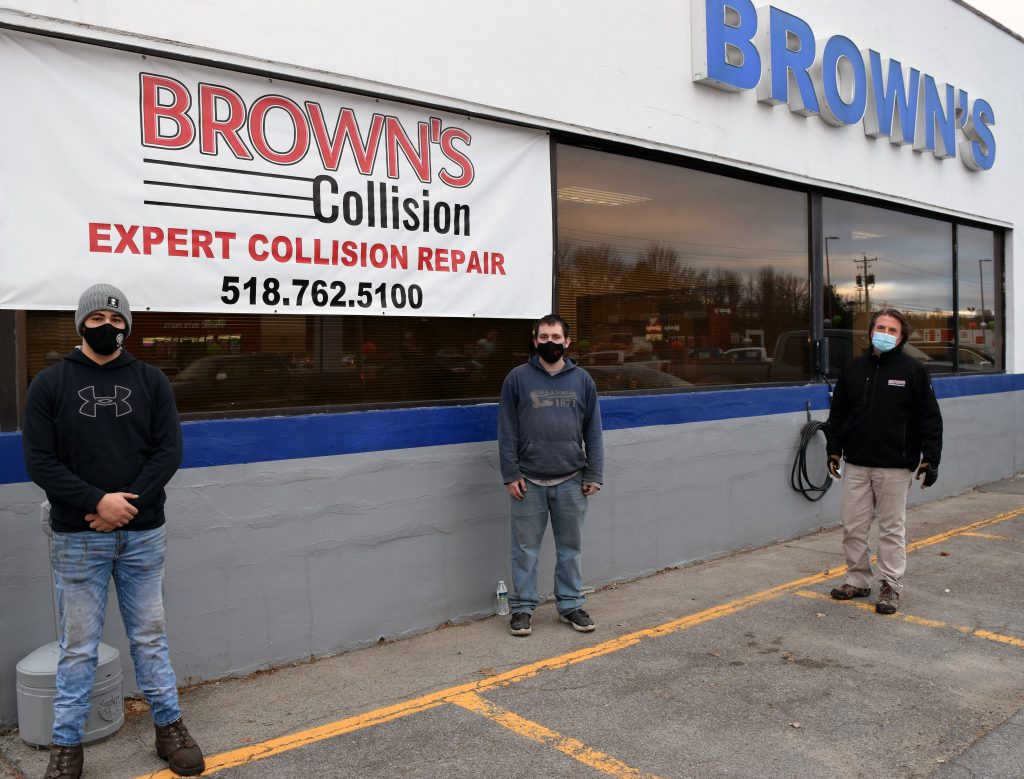 Three people stand outside of Brown's Ford in Johnstown posing for a photo,