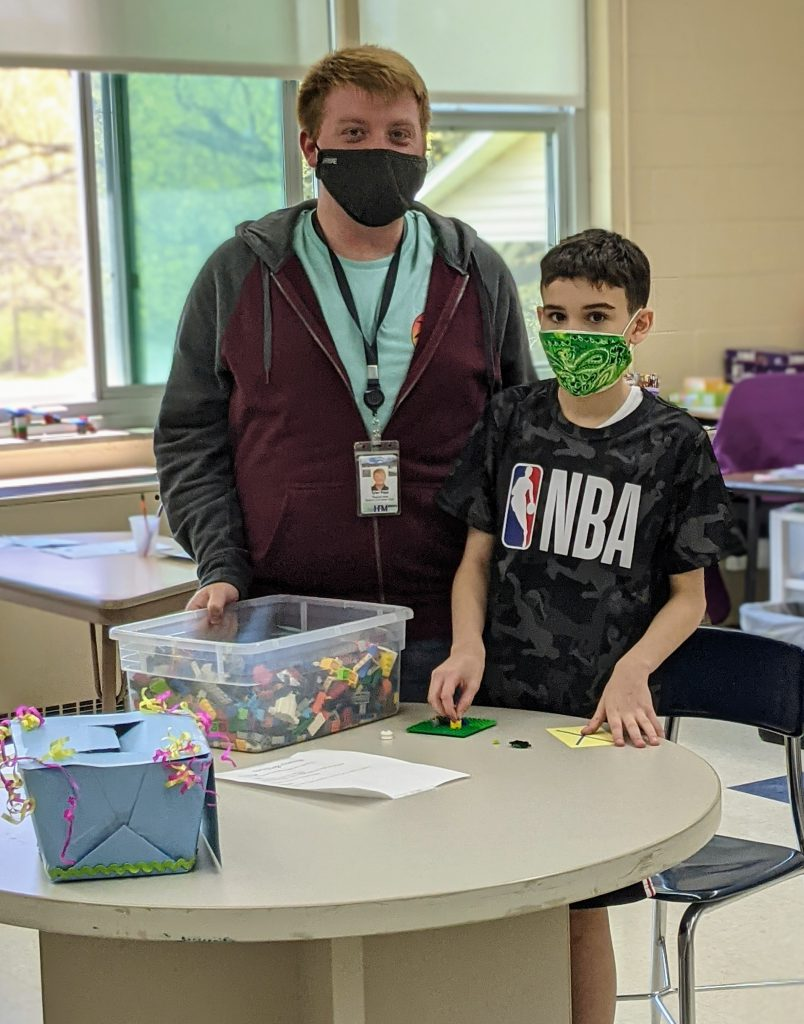 An adult and a student stand by a table with Legos on it